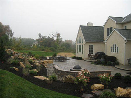 This beautiful and functional outdoor setting in Malvern includes a paver patio, fire pit, walls, landscaping lighting and a water feature