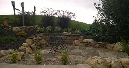 A cozy patio and retaining wall built into a hillside maximizes this Douglassville, PA home