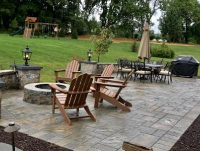 Downington outdoor living space provides separate areas for eating and relaxing around the fire pit.