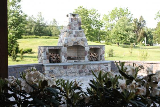Combination concrete and veneer wall surrounding patio and fireplace in Schwenksville, PA