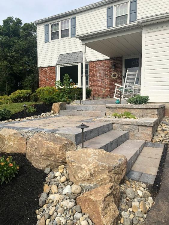 A front entrance walkway with a landing before final steps to front porch.