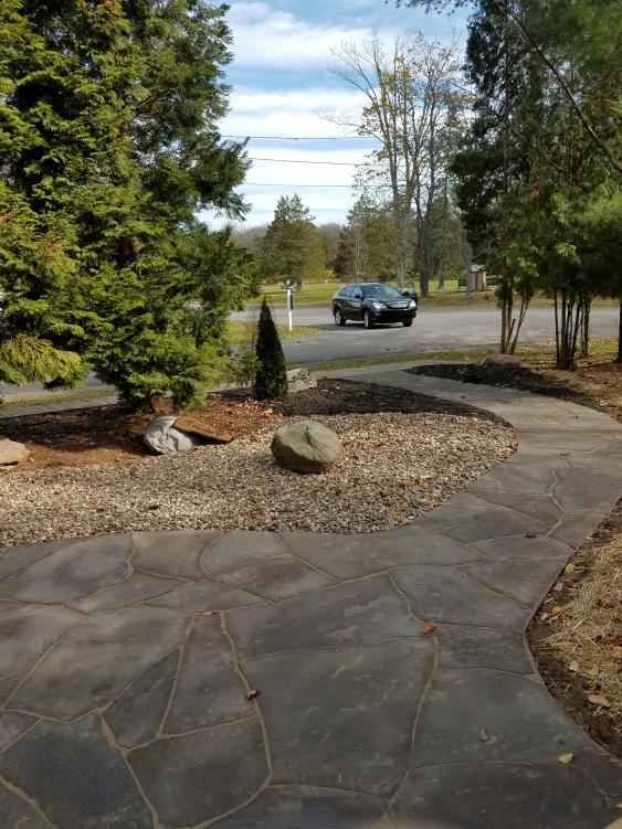 Hardscaping with river rock and Flagstone reduce maintenance tasks.