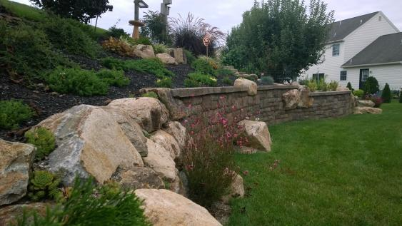 Combination of boulders and walls define the space and allow for plantings.