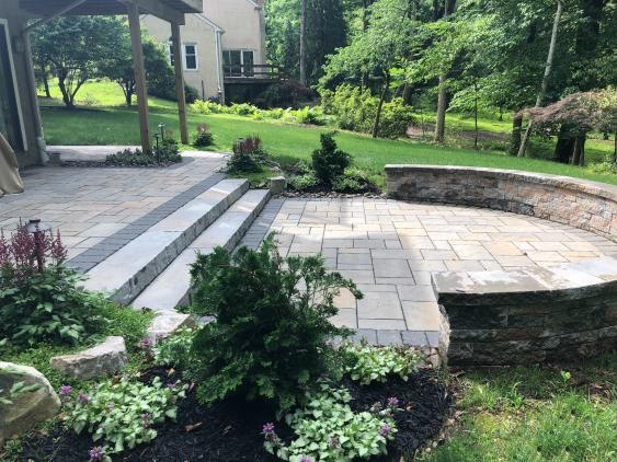 A patio with retaining wall in Wayne, PA designed and built by Whitehouse Landscaping