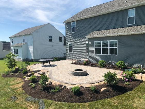 This curved patio in Douglassville is installed with Techo-bloc Blu 60 pavers and the shape lends itself well for seating around the firepit.