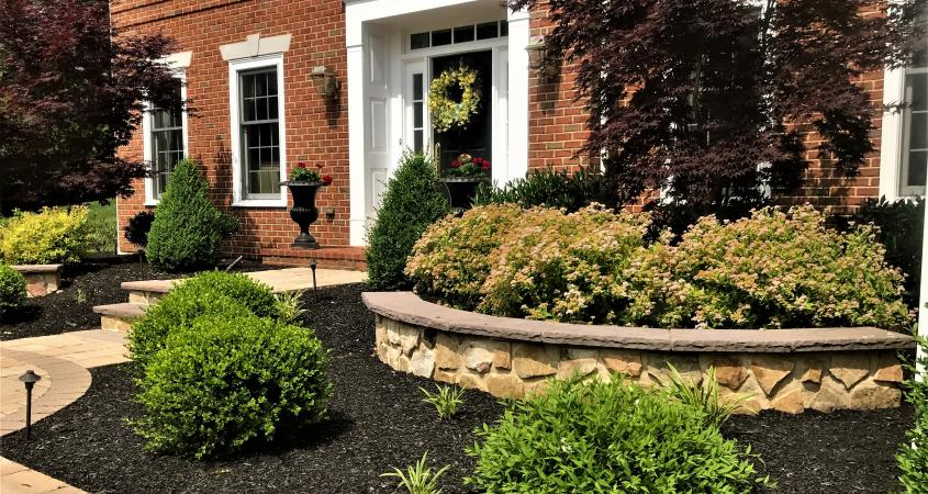 Stone veneer retaining wall with shrubs in Malvern, PA