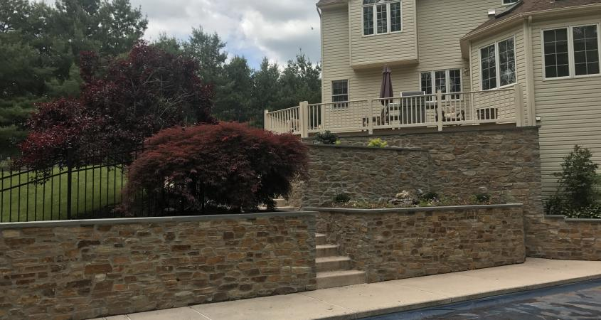 Stone veneer retaining wall and pool in Schwenksville, PA