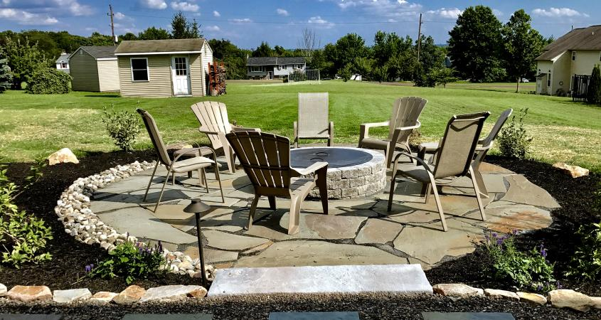 Fire pit in Gilbertsville, PA with chairs and flagstone pavers
