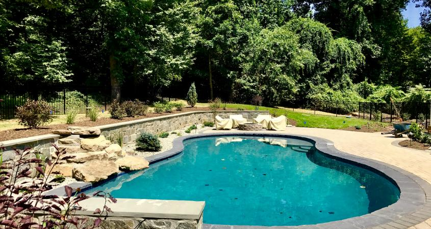 Stone veneer wall with patio pavers and pool in Glenmoore, PA