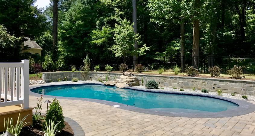 Inground pool with patio pavers and stone veneer retaining wall in Glenmoore