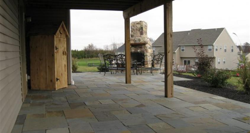 A flagstone patio and outdoor fireplace at this Gillbertsville, Pa home transformed this unused area in a great gathering space.