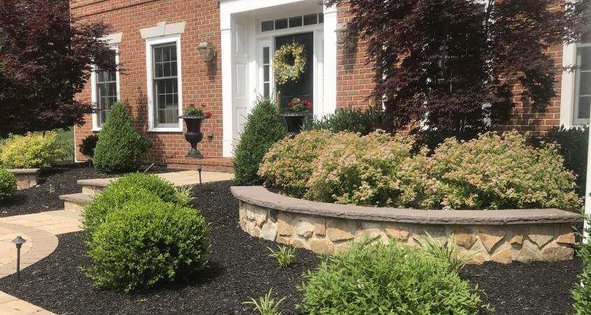 Curved stone wall and red brick colonial house in Malvern, PA