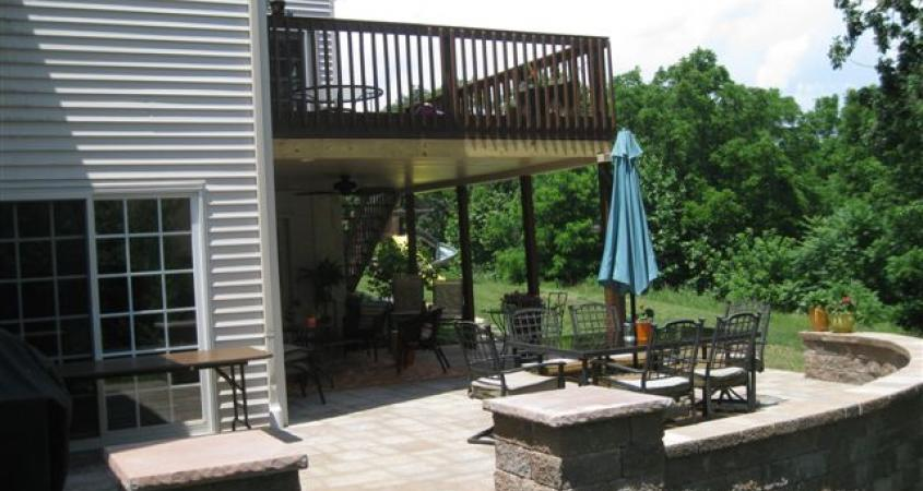 A paver patio installed under their deck with pillars and sitting wall doubled this Birdsboro, Pa. outdoor space.