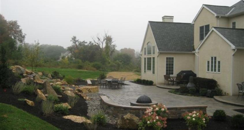 A gorgeous backyard in Malvern, Pa includes a paver patio, pondless waterfall, plantings, fire pit, witting wall and lighting.