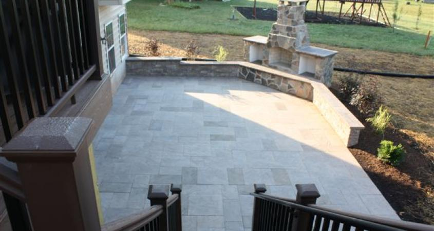 This Harleysville, Pa spacious paver patio includes an outdoor fireplace and sitting wall for entertaining.