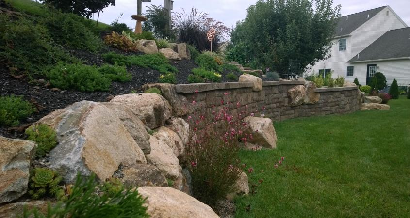 This retaining wall in Douglassville, Pa uses boulders and Techo-Bloc wall block to create visual interest while reinforcing a bank and controlling soil erosion.