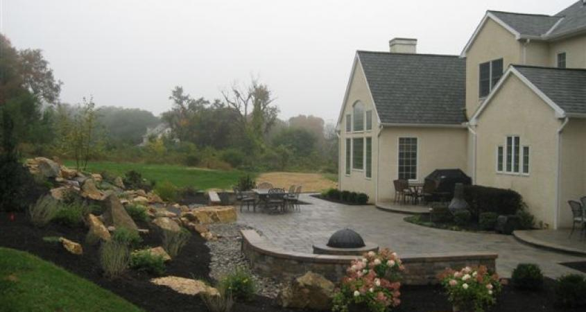 A curved Techo-Bloc sitting wall around a fire pit at this Malvern, Pa home is perfect for entertaining.