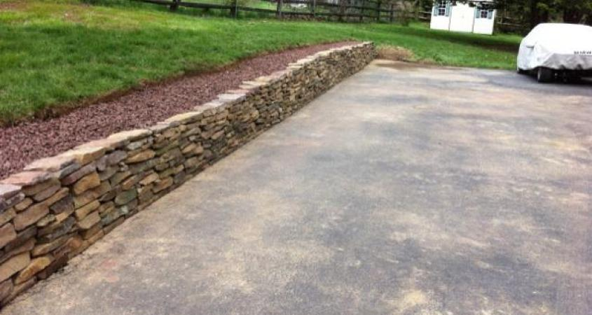 A dry stacked stone wall in Paoli, Pa  helps with rain runoff and erosion and gains  a level place to feature plantings.