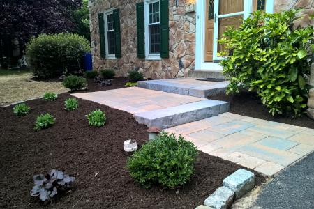 Walkway with shrubs and stone house in Limerick, PA