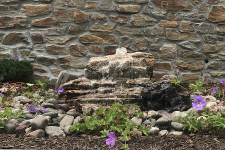Stone fountain in Schwenksville, PA with stone wall and petunia