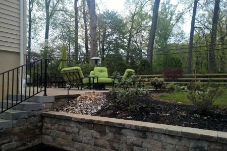 Retaining wall in Wayne, PA with shrubs and green chairs