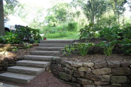A natural stone rock wall with a gentle curve in Sinking Spring, Pa adds an aesthetic element to the landscape.