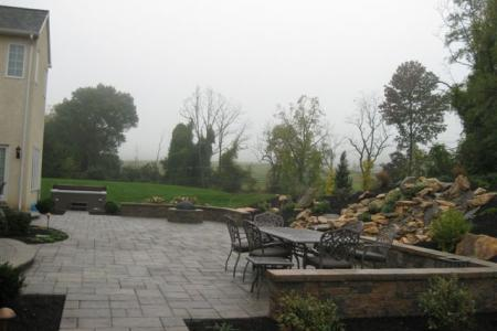 A sitting wall, firepit and a pondless waterfall compliment this wonderful paver patio in Malvern, Pa.