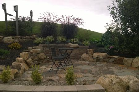 A combination of Techo-Bloc, boulders and natural wall stone creates a unique feel to this cozy patio area.