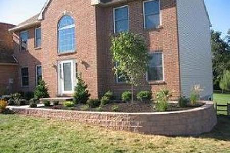 This retaining wall adds curb appeal to this Barto, Pa home and solves the headache of planting on a sloping yard.