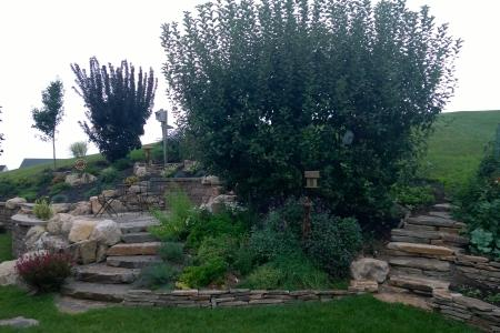 This tiered retaining wall in Douglassville, Pa features slab steps, increases useable space and focuses on plantings.