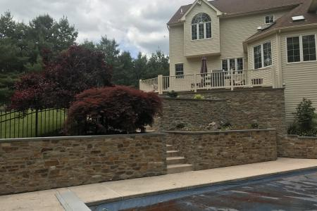 Stone retaining wall in Schwenksville, PA with pool and deck