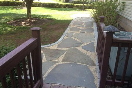 A flagstone walkway with Belgium Block edging in Schwenksville, Pa makes a nice landing area off the back deck.