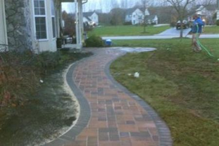A curved paver walkway with soldier border increases curb appeal for this Spring City, Pa home.