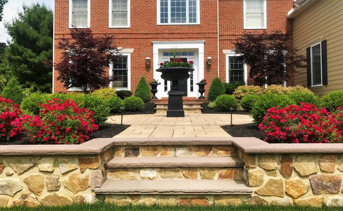 Stone veneer retaining wall and colonial house in Malvern, PA