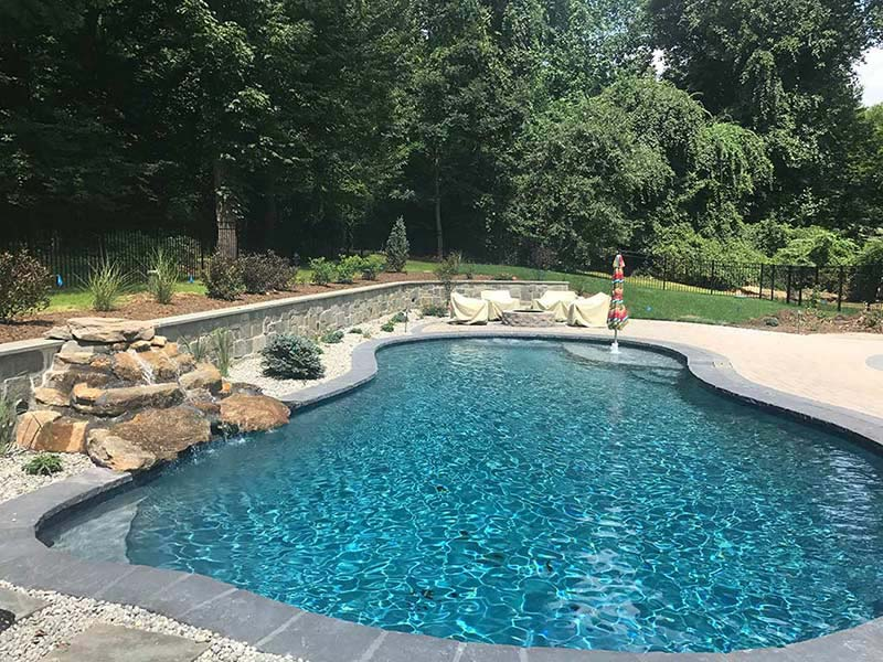Glenmoore pool installation with waterfall and landscaping