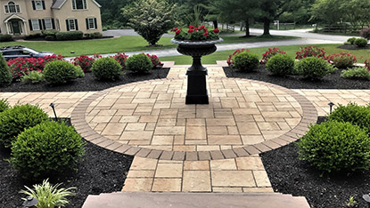 front yard landscaping with patio pavers and shrubs